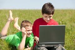 Deux garçons avec l'ordinateur portatif sur l'herbe Images libres de droits