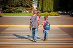 Deux garçons avec la marche de sac à dos, tenant dessus le jour chaud sur la route Photographie stock libre de droits