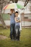 Deux garçons avec le parapluie d'arc-en-ciel en parc Photos libres de droits