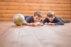 Deux garçons avec une boule se trouvant sur le plancher Photo stock