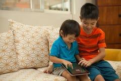 Deux garçons ayant l'amusement avec un comprimé numérique photographie stock libre de droits