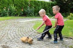 Deux garçons balayant la route de jardin avec de longues brosses de la poussière Images stock