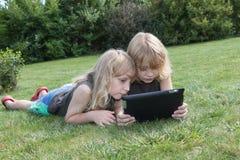 Deux garçons blonds regardent au comprimé photographie stock libre de droits
