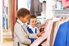 Deux garçons choisissent des vêtements dans le magasin tout en faisant des emplettes Photographie stock libre de droits