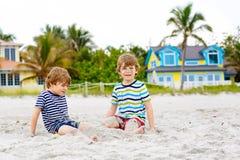 Deux garçons d'enfant construisant le sable se retranchent sur la plage tropicale photo stock