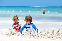 Deux garçons d'enfant construisant le sable se retranchent sur la plage tropicale de Bora Bora Image libre de droits