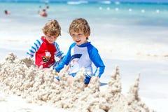Deux garçons d'enfant construisant le sable se retranchent sur la plage tropicale de Bora Bora Photo stock