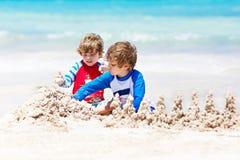 Deux garçons d'enfant construisant le sable se retranchent sur la plage tropicale de Bora Bora Photographie stock libre de droits