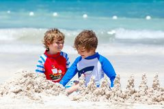 Deux garçons d'enfant construisant le sable se retranchent sur la plage tropicale de Mexiko Images stock