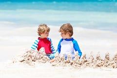 Deux garçons d'enfant construisant le sable se retranchent sur la plage tropicale de Tulum, Mexique Photographie stock libre de droits