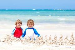 Deux garçons d'enfant construisant le sable se retranchent sur la plage tropicale du Playa del Carmen, Mexique Images stock