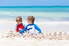 Deux garçons d'enfant construisant le sable se retranchent sur la plage tropicale du Playa del Carmen, Mexique Photo libre de droits