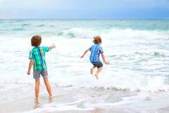 Deux garçons d'enfant courant sur l'océan échouent en Floride Photographie stock