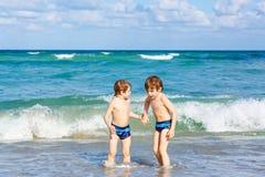 Deux garçons d'enfant courant sur l'océan échouent en Floride Photos stock