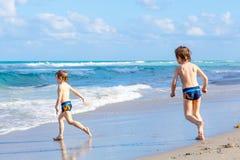 Deux garçons d'enfant courant sur l'océan échouent en Floride Photographie stock libre de droits