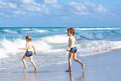 Deux garçons d'enfant courant sur l'océan échouent en Floride Photo stock