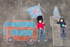 Deux garçons d'enfant dans l'uniforme britannique de policier de soldat avec Londres pi Image stock
