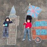 Deux garçons d'enfant dans l'uniforme britannique de policier de soldat avec Londres pi Photos libres de droits