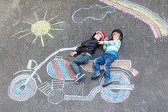 Deux garçons d'enfant dans le casque avec la moto décrivent le dessin avec le colo Photos stock