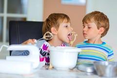 Deux garçons d'enfant faisant le gâteau cuire au four dans la cuisine domestique Photographie stock libre de droits