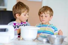 Deux garçons d'enfant faisant le gâteau cuire au four dans la cuisine domestique Photos libres de droits