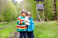 Deux garçons d'enfant marchant par la forêt le jour froid Photo stock