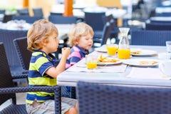 Deux garçons d'enfant prenant le petit déjeuner sain dans le restaurant Images stock