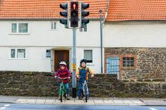 Deux garçons d'enfants faisant du vélo et attendant sur le feu de signalisation Photo libre de droits