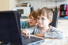 Deux garçons d'enfants jouant en ligne et surfant dans l'Internet sur l'ordinateur Image stock