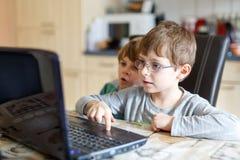 Deux garçons d'enfants jouant en ligne et surfant dans l'Internet sur l'ordinateur Photos libres de droits