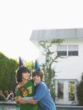 Deux garçons dans des chapeaux de partie jouant en Front Of House Images libres de droits