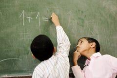 Deux garçons dans la salle de classe pensant, écrivant et counti Image libre de droits