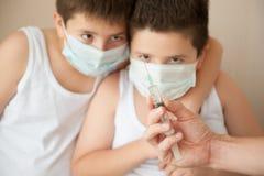 Deux garçons dans le masque chirurgical regardant la main avec la seringue Photographie stock