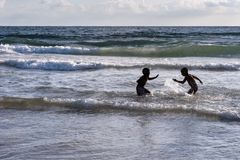 Deux garçons dans un combat de l'eau dans le ressac du méditerranéen image stock