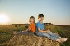 Deux garçons dans une meule de foin dans le domaine Photo libre de droits