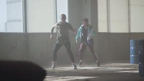 Deux garçons dansant devant la grande fenêtre dans le bâtiment abandonné Adolescents entreprenant la démarche de danse simultaném banque de vidéos