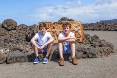 Deux garçons de l'adolescence s'asseyant sur une roche et ont un reste Photo stock