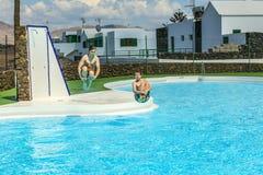 Deux garçons de l'adolescence sautent dans la piscine Photo libre de droits