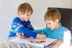 Deux garçons de petit enfant à l'école peignant une histoire avec les stylos colorés Images libres de droits
