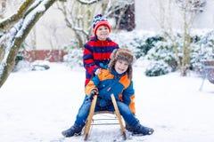 Deux garçons de petit enfant appréciant le traîneau montent en hiver Photos stock
