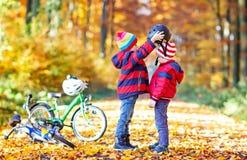 Deux garçons de petit enfant avec des bicyclettes dans la forêt d'automne mettant des casques Photos libres de droits