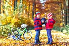 Deux garçons de petit enfant avec des bicyclettes dans la forêt d'automne mettant des casques Images libres de droits