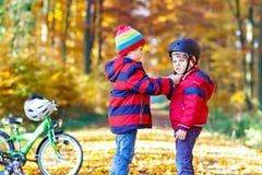 Deux garçons de petit enfant avec des bicyclettes en automne se garent Photo stock