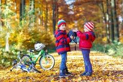 Deux garçons de petit enfant avec des bicyclettes en automne se garent Photographie stock