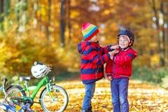 Deux garçons de petit enfant avec des bicyclettes en automne se garent Image stock