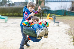 Deux garçons de petit enfant ayant l'amusement avec l'oscillation à chaînes sur le terrain de jeu extérieur Photographie stock libre de droits