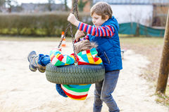 Deux garçons de petit enfant ayant l'amusement avec l'oscillation à chaînes sur le terrain de jeu extérieur Photos libres de droits