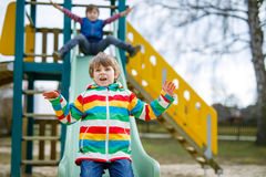 Deux garçons de petit enfant ayant l'amusement et glissant sur le terrain de jeu extérieur Image stock