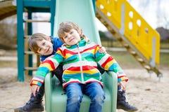 Deux garçons de petit enfant ayant l'amusement et glissant sur le terrain de jeu extérieur Photographie stock libre de droits