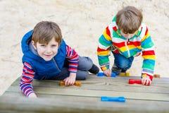 Deux garçons de petit enfant ayant l'amusement et s'élevant sur le terrain de jeu extérieur Image stock